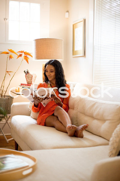 Woman laying on couch reading a magazine - Colorstock™  © Latoya Dixon  - diverse stock photos