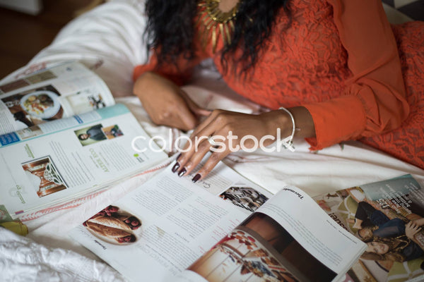 Woman laying on the bed reading magazine - Colorstock™  © Latoya Dixon  - diverse stock photos