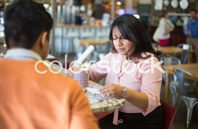 Woman looking at business card - Colorstock™  © Shea Parikh  - diverse stock photos
