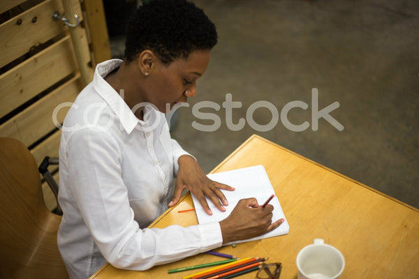 Woman sketching designs (overhead view) - Colorstock™  © Shea Parikh  - diverse stock photos