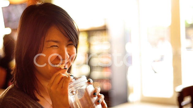 Woman smiling while drinking - Colorstock™  © David Huff  - diverse stock photos