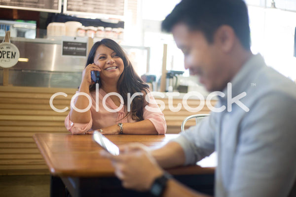 Woman talking on smartphone at cafe - Colorstock™  © Shea Parikh  - diverse stock photos