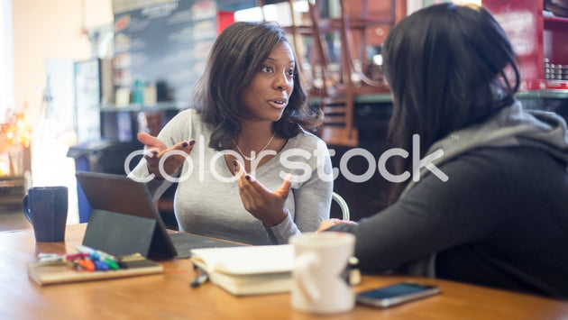 Woman talking to friend at a cafe - Colorstock™  © Shea Parikh  - diverse stock photos