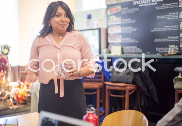 Woman talking to her friends at a restaurant - Colorstock™  © Shea Parikh  - diverse stock photos