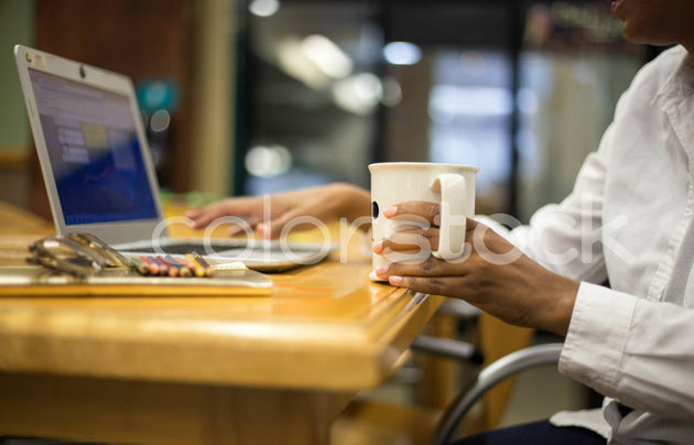 Woman working while holding tea - Colorstock™  © Shea Parikh  - diverse stock photos