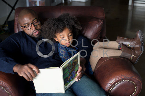 Dad and daughter on couch reading a book, Some Sweet Photography - Colorstock: diverse stock photos