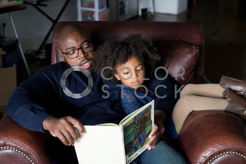 Dad and daughter on couch reading a book -2, Some Sweet Photography - Colorstock: diverse stock photos