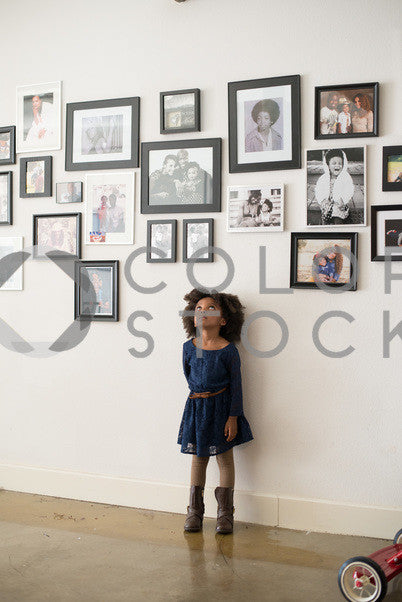 Child standing under family photos, Some Sweet Photography - Colorstock: diverse stock photos