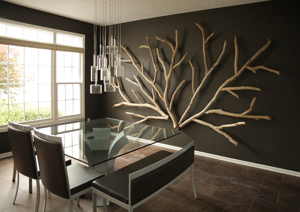 A driftwood wall art installation by Susie Frazier feels like sprawling tree branches on an interior wall.