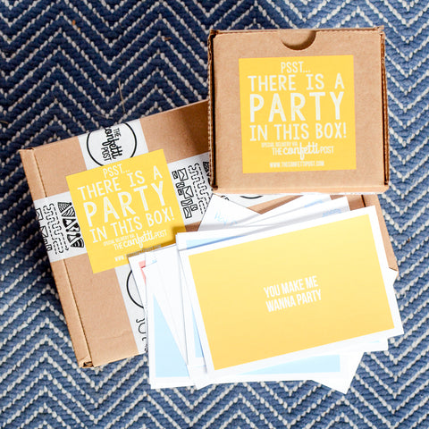 Party in a box gift packages stacked with free downloadable, printable happy mail postcards