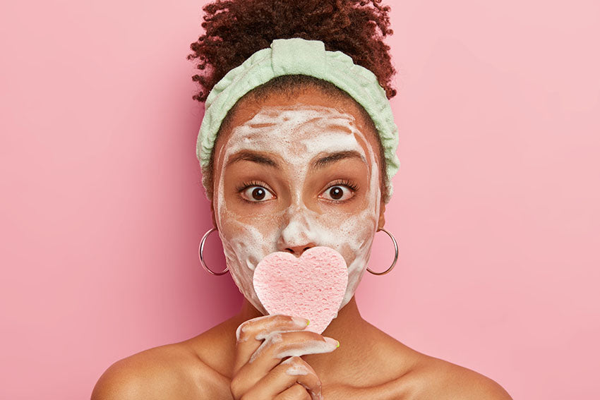 Diverse woman, with a face lathererd in facial cleanser using a textured soft cleansing sponge