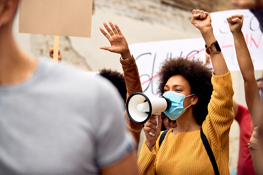 African American woman activist utilizing a megaphone within a crowd