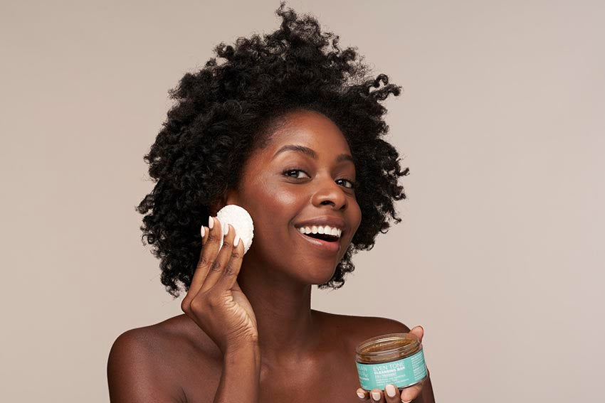 African American woman smiling while using the Even Tone Cleansing Bar and accompanying sponge