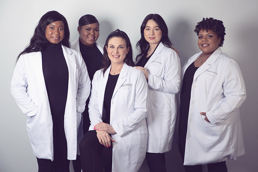 Urban Skin Rx® diverse team of aestiticians posing with founder Rachel Roff who specializes in treating melanated skin