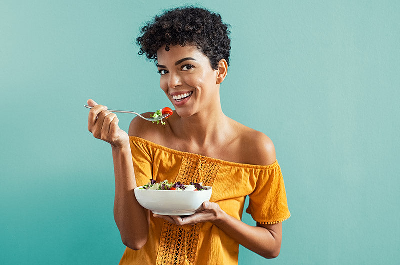 beautiful young african american woman smiling and eating
