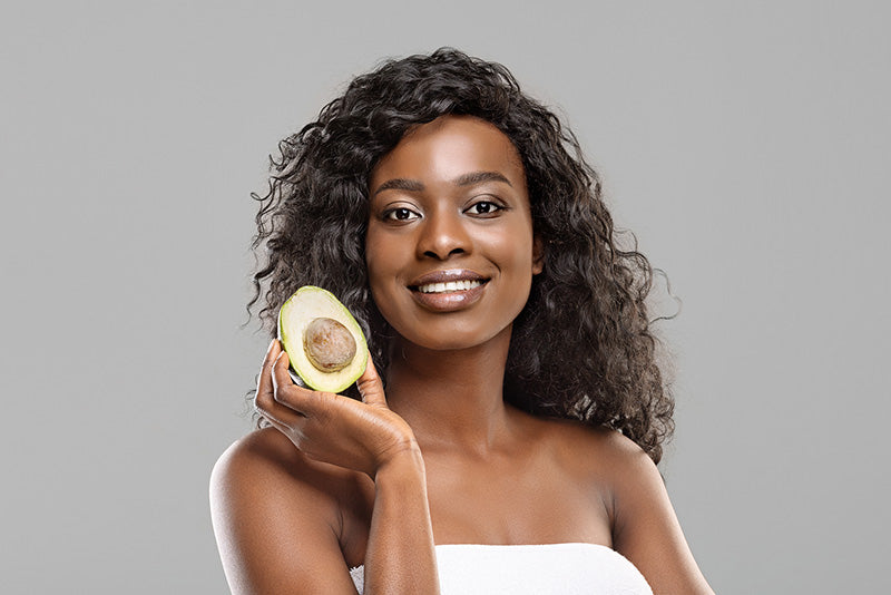 african american woman holding up avocado