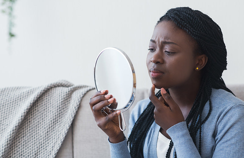 young black woman checking mirror upset at breakout