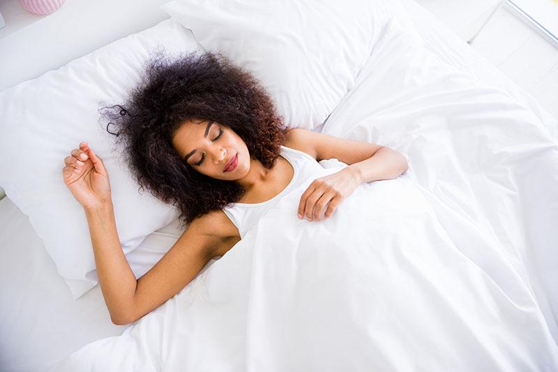 dark skinned woman resting comfortably in bed