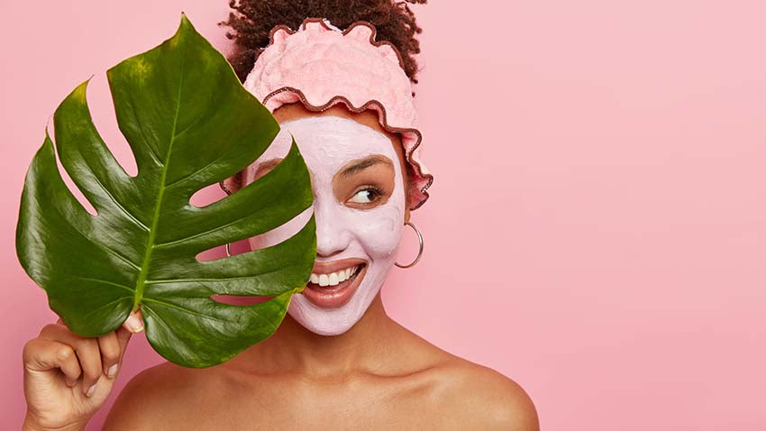 happy young woman applies facial mud mask on face for removing wrinkles or fine lines