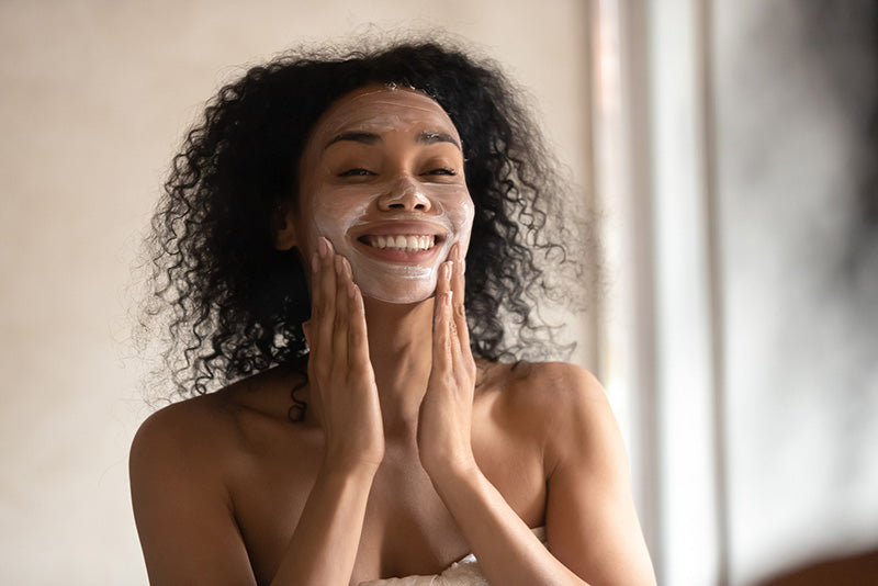 smiling woman applying face mask