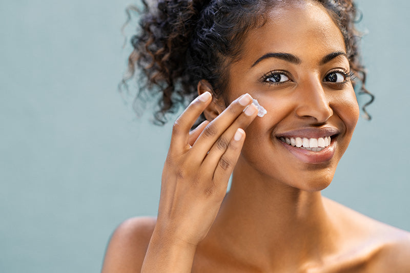 young pretty woman smiling as she applies facial cream
