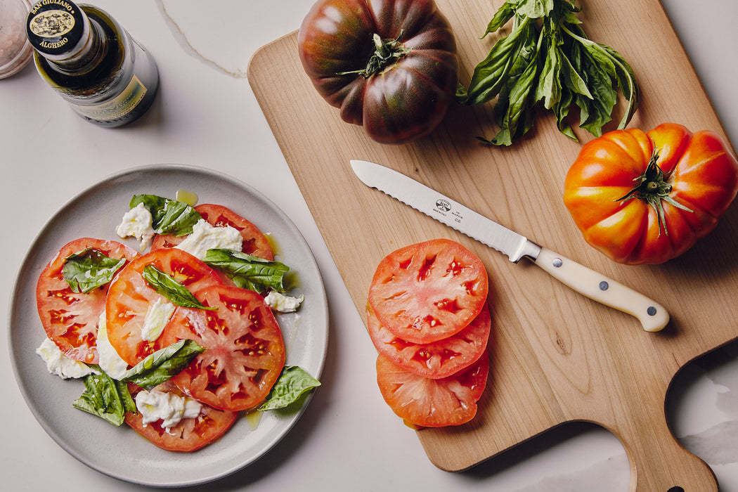 White Tomato Knife - Aerial View on Cutting Board with Tomatoes