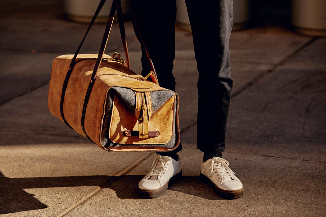 Orox Leather Co. Ryoko Duffel - Sand - man holding bag on a sunny sidewalk
