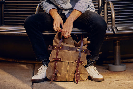 Orox Leather Co. Parva Rucksack - Brown - man opening the bag in front of him as he sits on a bench