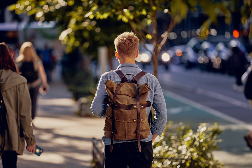 Orox Leather Co. Parva Rucksack - Brown - another view of man wearing the backpack as he walks down the street