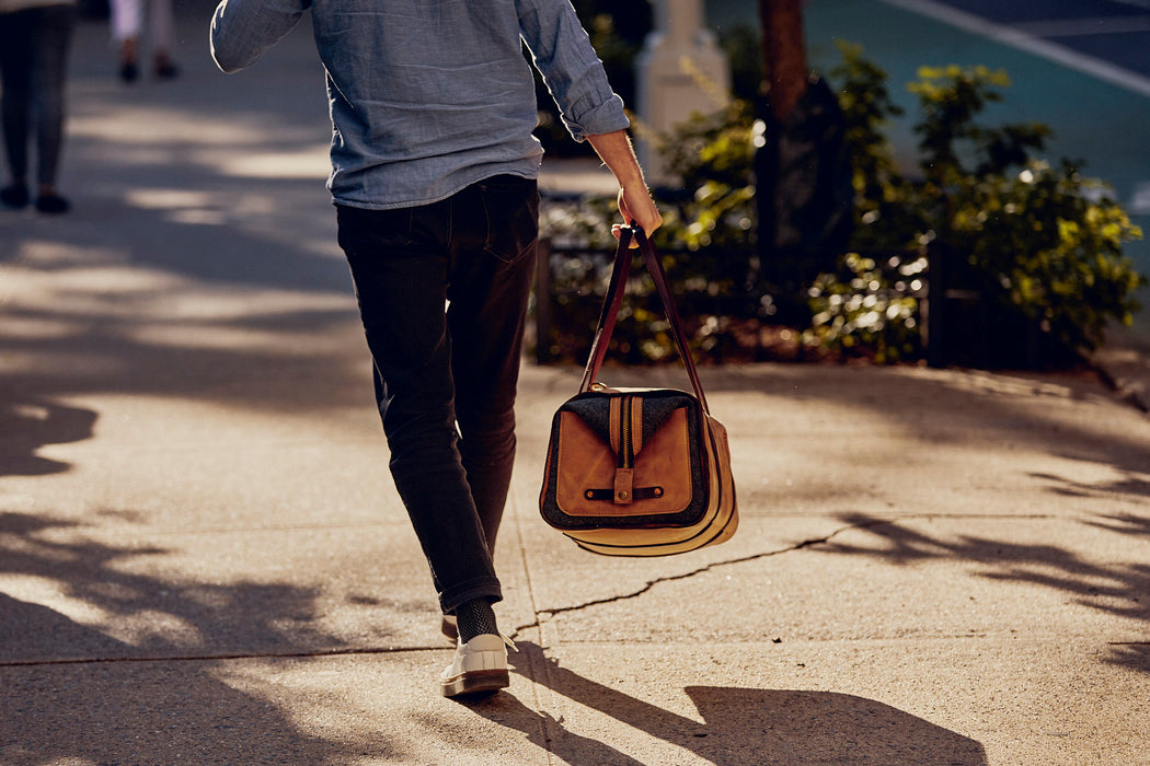 Orox Leather Co. Ryoko Duffel - Sand - back view of bag walking down the street holding duffel