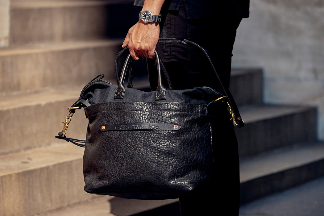 Orox Leather Co. Viator Tote Bag - Black - man holding the bag by the short handles as he approaches a set of stairs