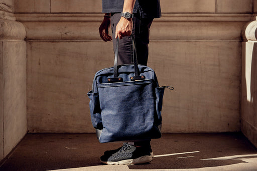 Orox Leather Co. Viator Carryall Bag- Denim - side view of man holding the bag by the handles