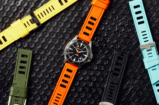One watch with an ISOfrane watch strap in orange, surrounded by straps in yellow, green, black, and blue