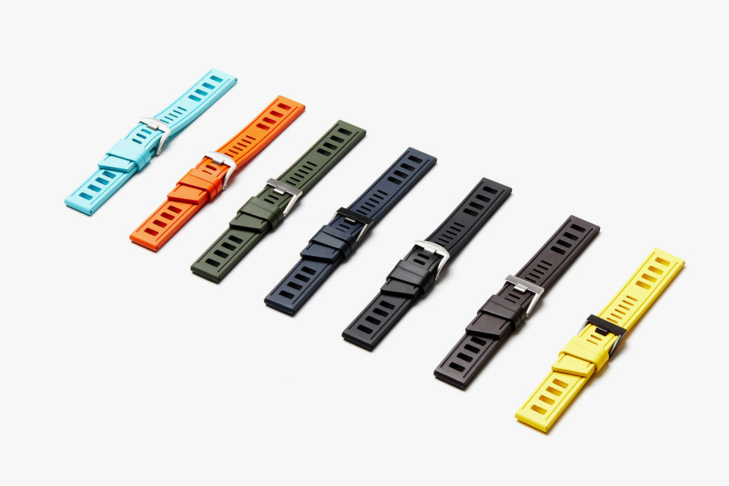Group of 7 ISOfrane watch straps laying flat: light blue, orange, green, dark blue, black, gray, and yellow