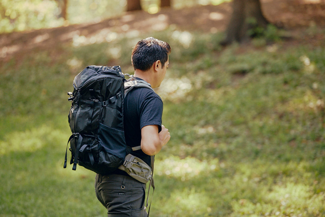 Mystery Ranch Scree 32 Backpack - Black - side profile view of a man walking up a hill wearing the bcakpack