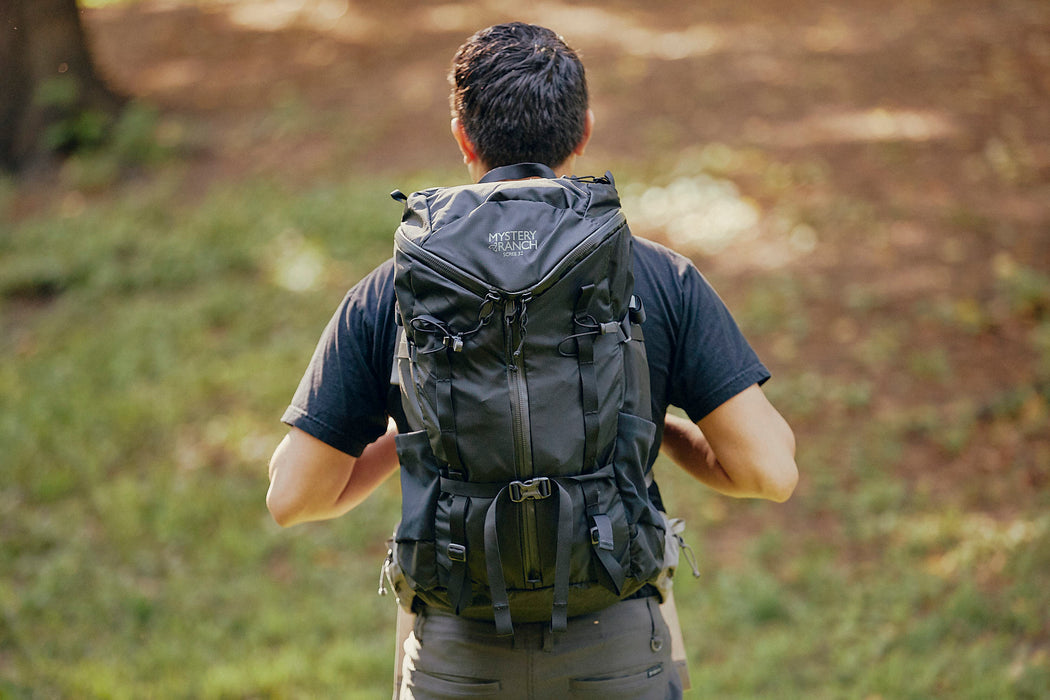 Mystery Ranch Scree 32 Backpack - Black - image of man wearing backpack as he walks into woods