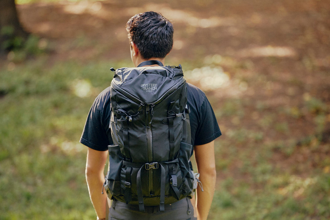 Mystery Ranch Scree 32 Backpack - Black - man wearing backpack and walking in the woods