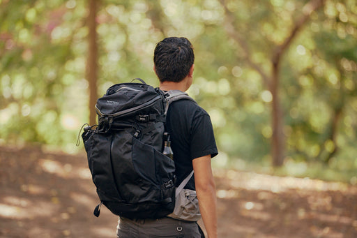 Mystery Ranch Coulee 40 Backpack - Black - image of man wearing backpack as he walks into woods