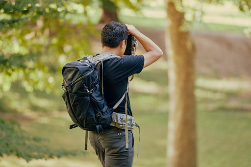 Mystery Ranch Coulee 25 Backpack- Black - side view of man wearing backpack as he aims a camera toward woods