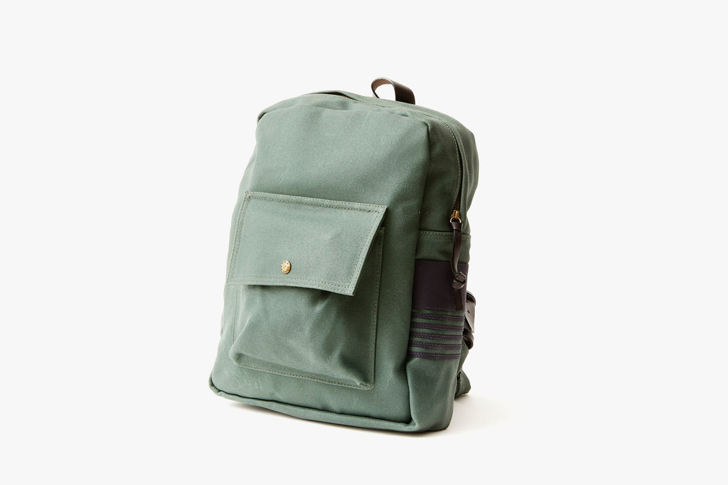 Pine Long Wharf Supply Co. Ipswich Day Backpack - Pine - side view of backpack standing up, showing front pocket with a gold-toned snap closure and brown leather detailing on the side panel