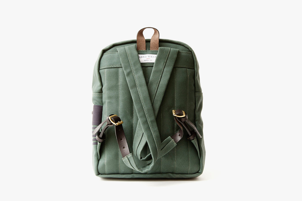 Pine Long Wharf Supply Co. Ipswich Day Backpack - Pine - back view, showing shoulder straps criss-crossed and also showing leather detailing