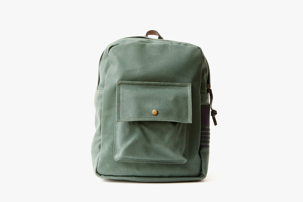Pine Long Wharf Supply Co. Ipswich Day Backpack - Pine - front view of backpack standing up, showing front pocket with a gold-toned snap closure