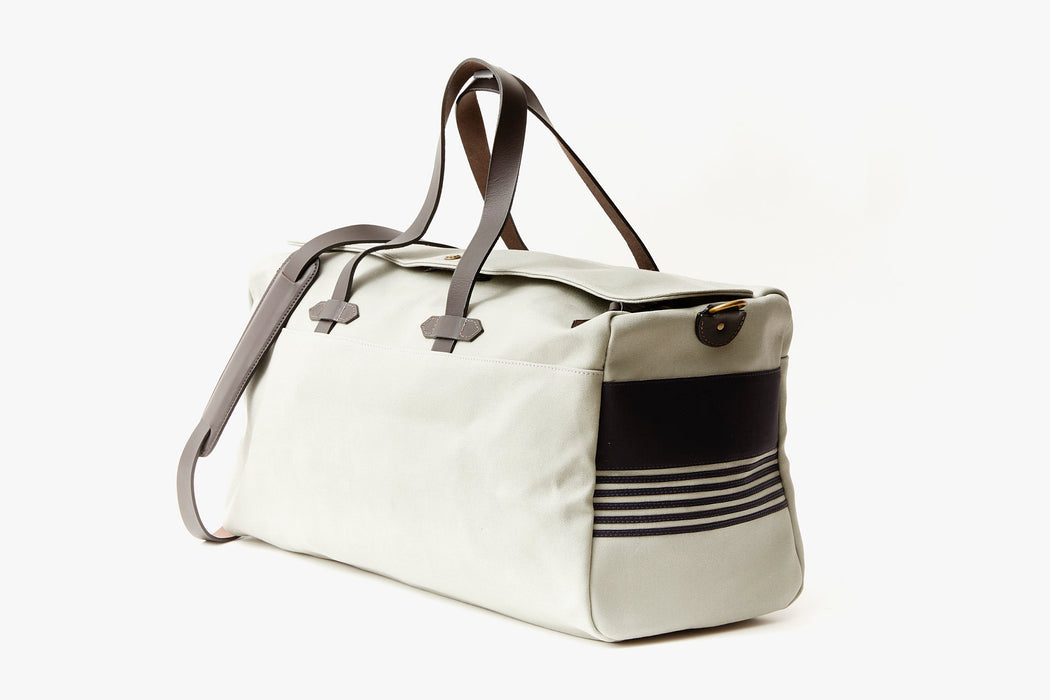 Long Wharf Supply Co. Ipswich Weekender Bag - Grey - side view of duffel standing upright, showing top handles and shoulder strap