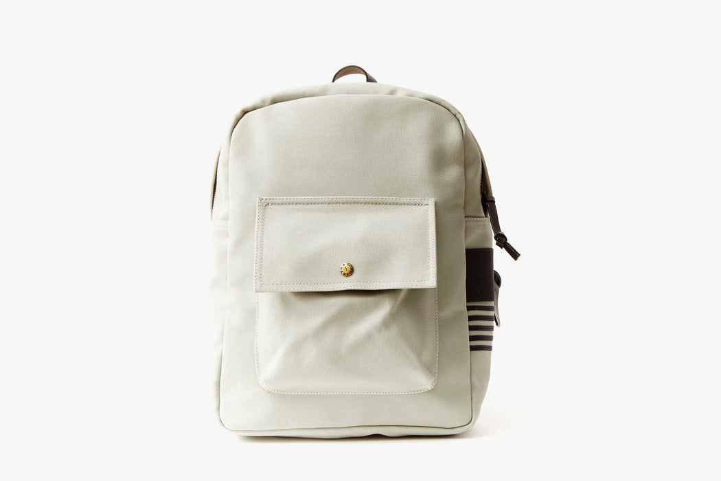Grey Long Wharf Supply Co. Ipswich Day Backpack - Grey - front view of backpack standing up, showing front pocket with a gold-toned snap closure