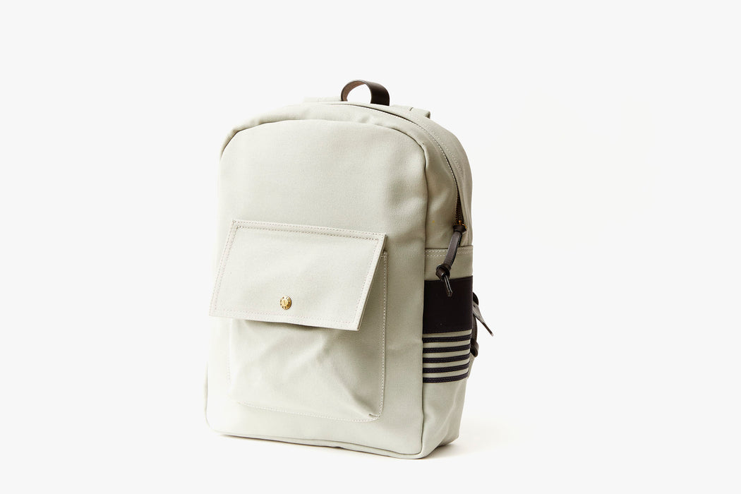 Grey Long Wharf Supply Co. Ipswich Day Backpack - Grey - side view of backpack standing up, showing front pocket with a gold-toned snap closure and brown leather detailing on the side panel