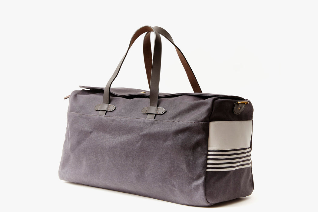 Long Wharf Supply Co. Ipswich Weekender Bag - Navy  - side view of duffel standing upright showing top handles and shoulder strap