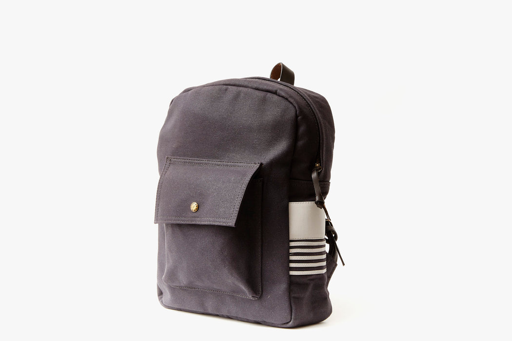 Navy Long Wharf Supply Co. Ipswich Day Backpack - Navy - side view of backpack standing up, showing front pocket and white leather detailing on the side panel