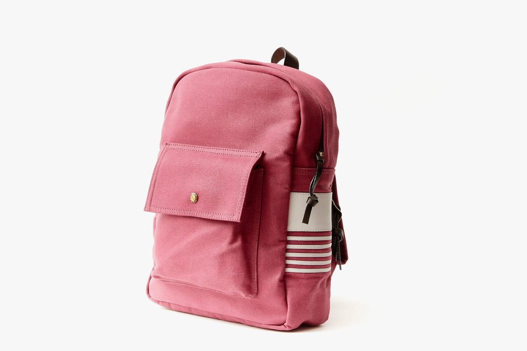 Maroon Long Wharf Supply Co. Ipswich Day Backpack - Maroon - side view of backpack standing up, showing front pocket with a gold-toned snap closure and white leather detailing on side panel