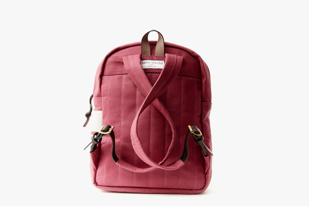 Maroon Long Wharf Supply Co. Ipswich Day Backpack - Maroon - back view, showing shoulder straps criss-crossed and also showing brown leather detailing