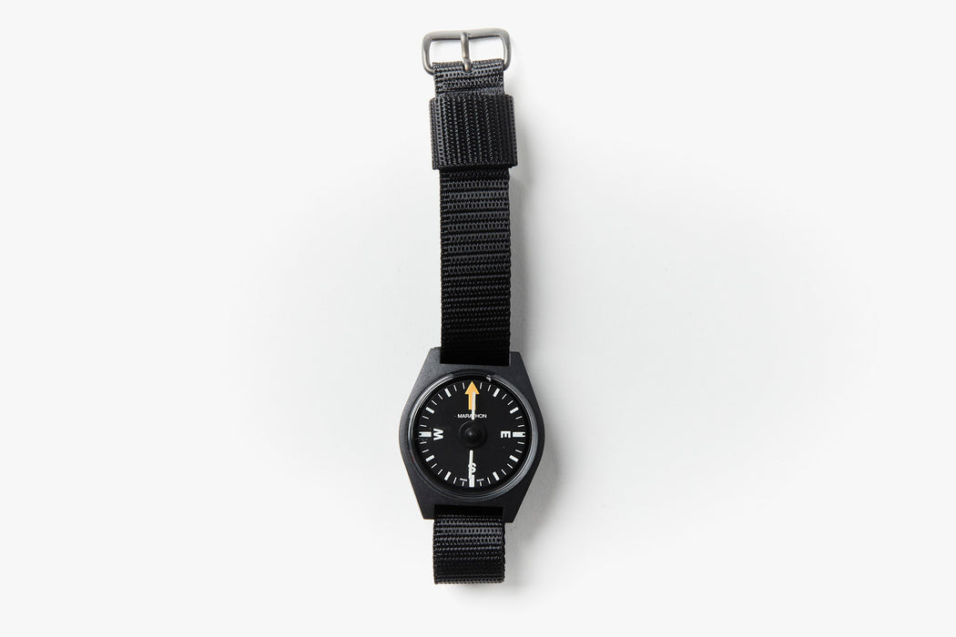 Marathon Unmounted Glow In The Dark Wrist Compass - Black - compass with NATO strap laying down on a white surface